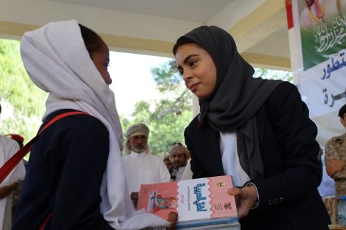 Nada al-Ahdal giving textbooks to young girls
