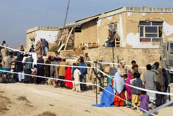 Villagers line up with army tanks